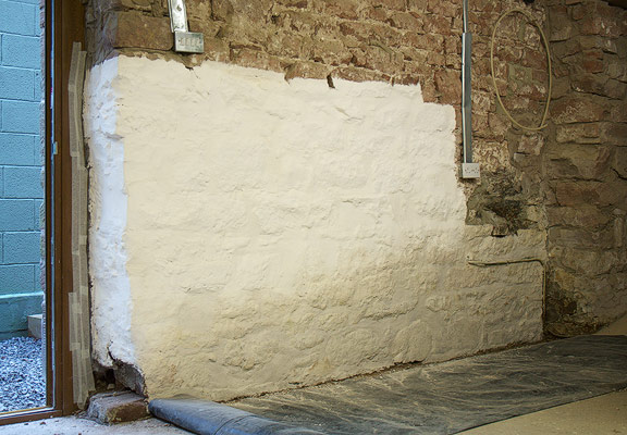 limewashed sandstone wall with excessive damp problems