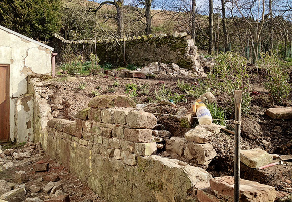 retaining wall of rubble stone and lime mortar under construction